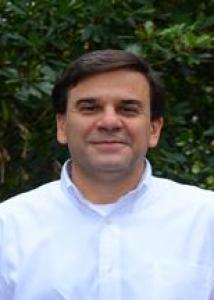 Headshot of Mark with short dark hair and white shirt.