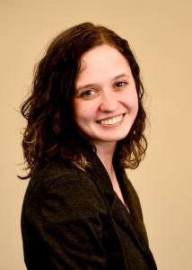 Headshot of  Mary McCauley. Short brown hair, and black blazer.