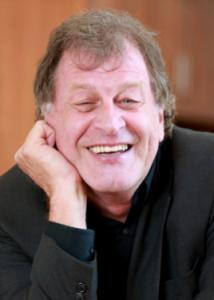 Headshot of Peter Molenaar with light brown hair, black shirt, and dark gray jacket.