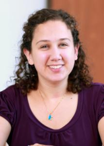 Headshot of Rachel Koffer with curly brown hair and purple blouse.