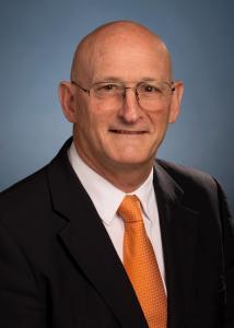 Headshot of Richard Roush with bald head, glasses, white shirt, orange tie, and black jacket.