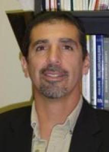 Headshot of Robert Turrisi with short black hair, goatee, white shirt, and black jacket.