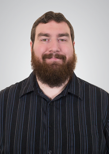 Headshot of Russel Houtz with long beard in front of a grey background wearing a black top.