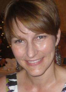 Headshot of Suzy Scherf with short brown hair, long silver earrings, and black and white patterned top.