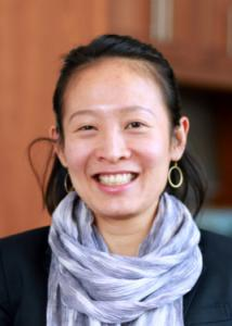 Headshot of Sy-Miin Chow with long black hair, black blouse, purple scarf, and gold hoop earrings.