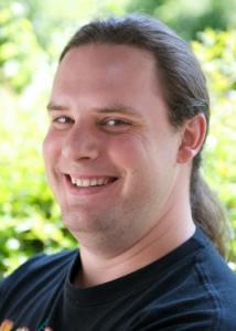 Headshot of Timothy Brick with long brown hair and black shirt.